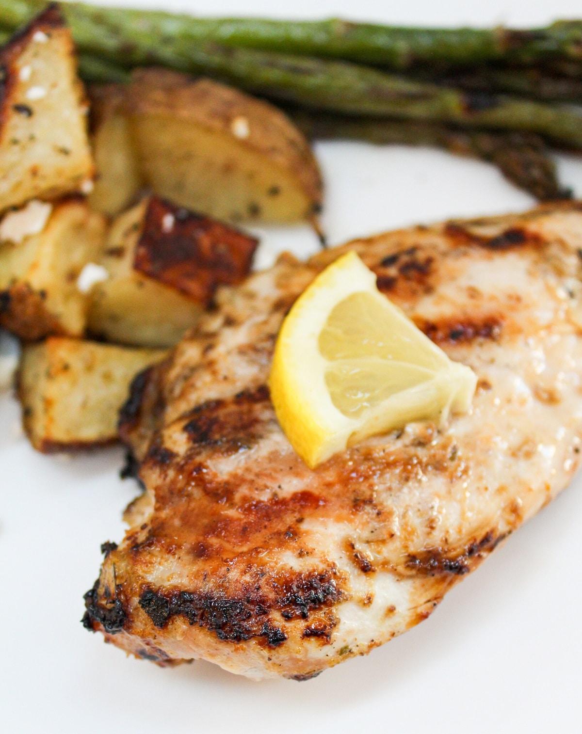 grilled lemon pepper chicken on white plate with sliced lemon