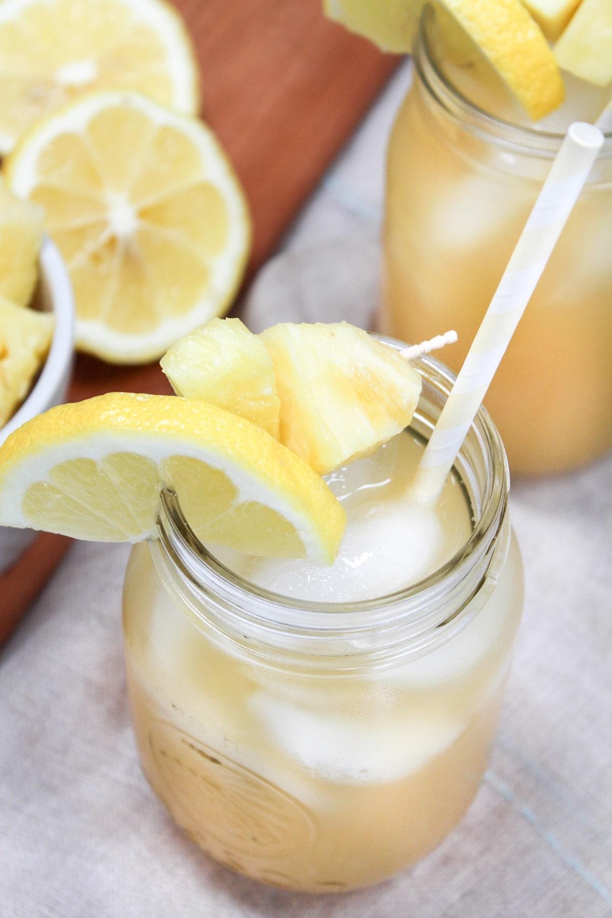 pineapple bourbon lemonade in glass with pineapple and lemon garnish