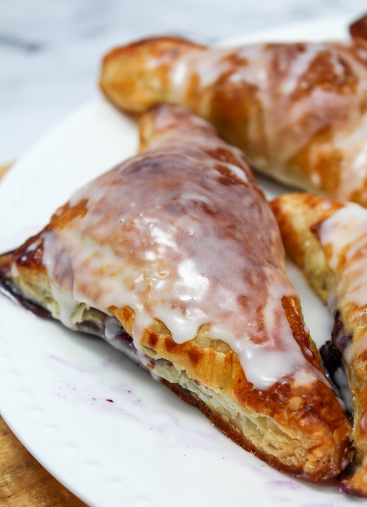 cooked blueberry turnover with frosting on a white plate