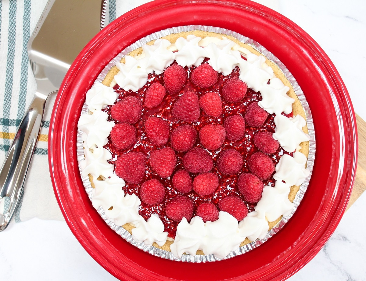 overhead photo of raspberry cream pie with red serving dish