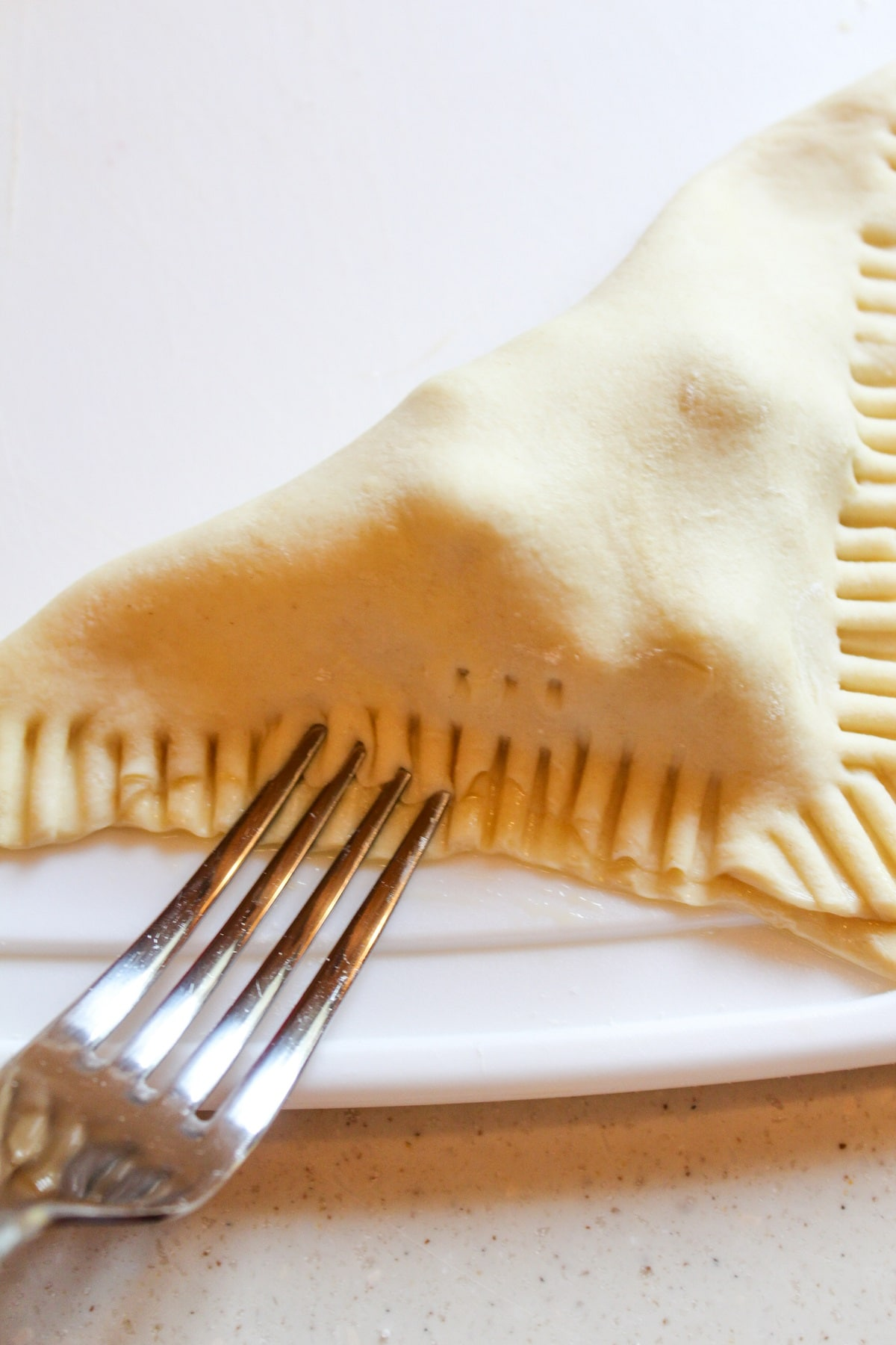 sealing edges of dough with a fork
