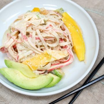 spicy kani salad on a plate with mango and avocado slices