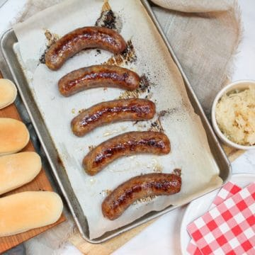overhead photo of oven baked brats on a baking sheet with buns on the side and a bowl of sauerkraut.