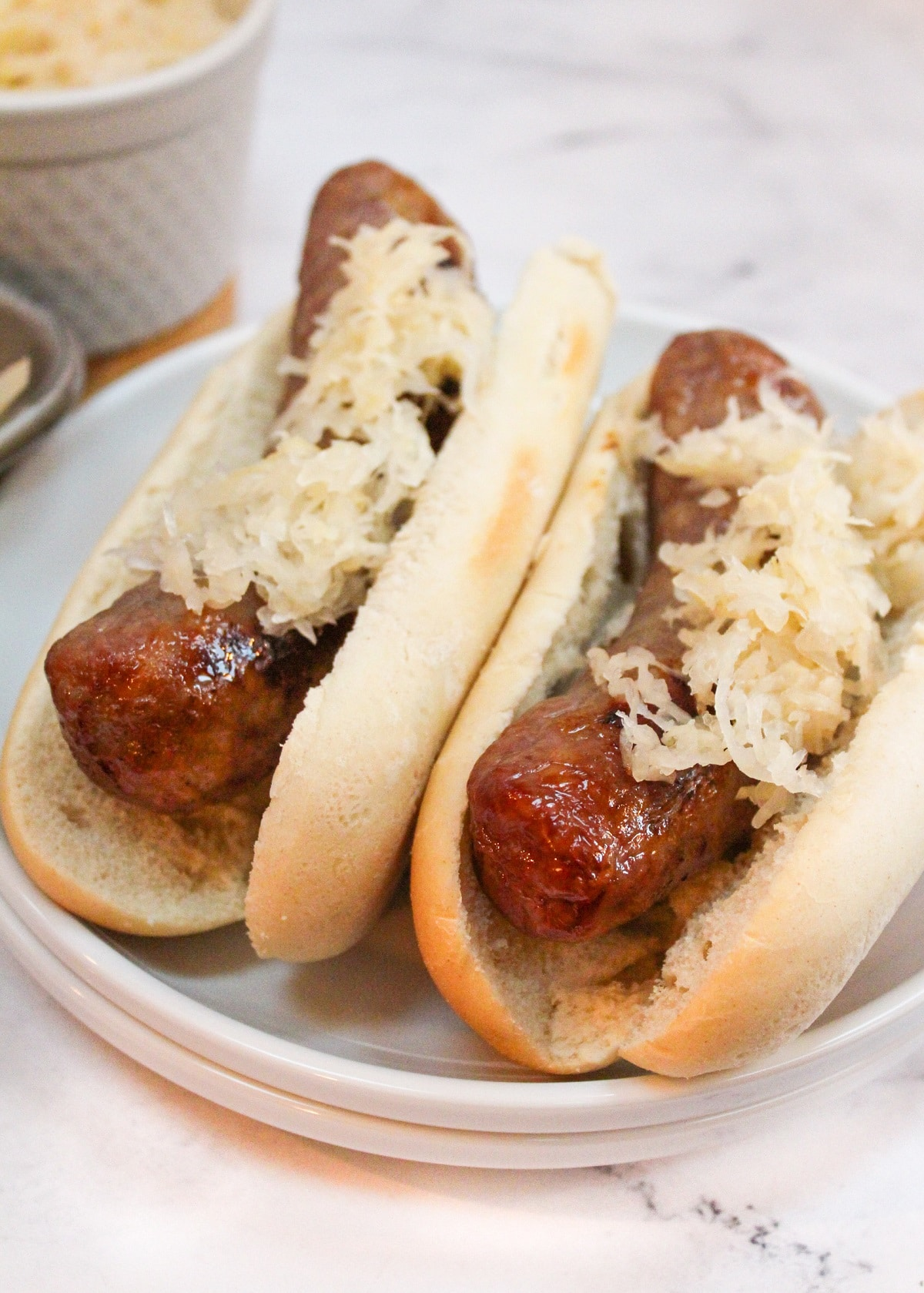 brats in a bun with sauerkraut on top on a white plate