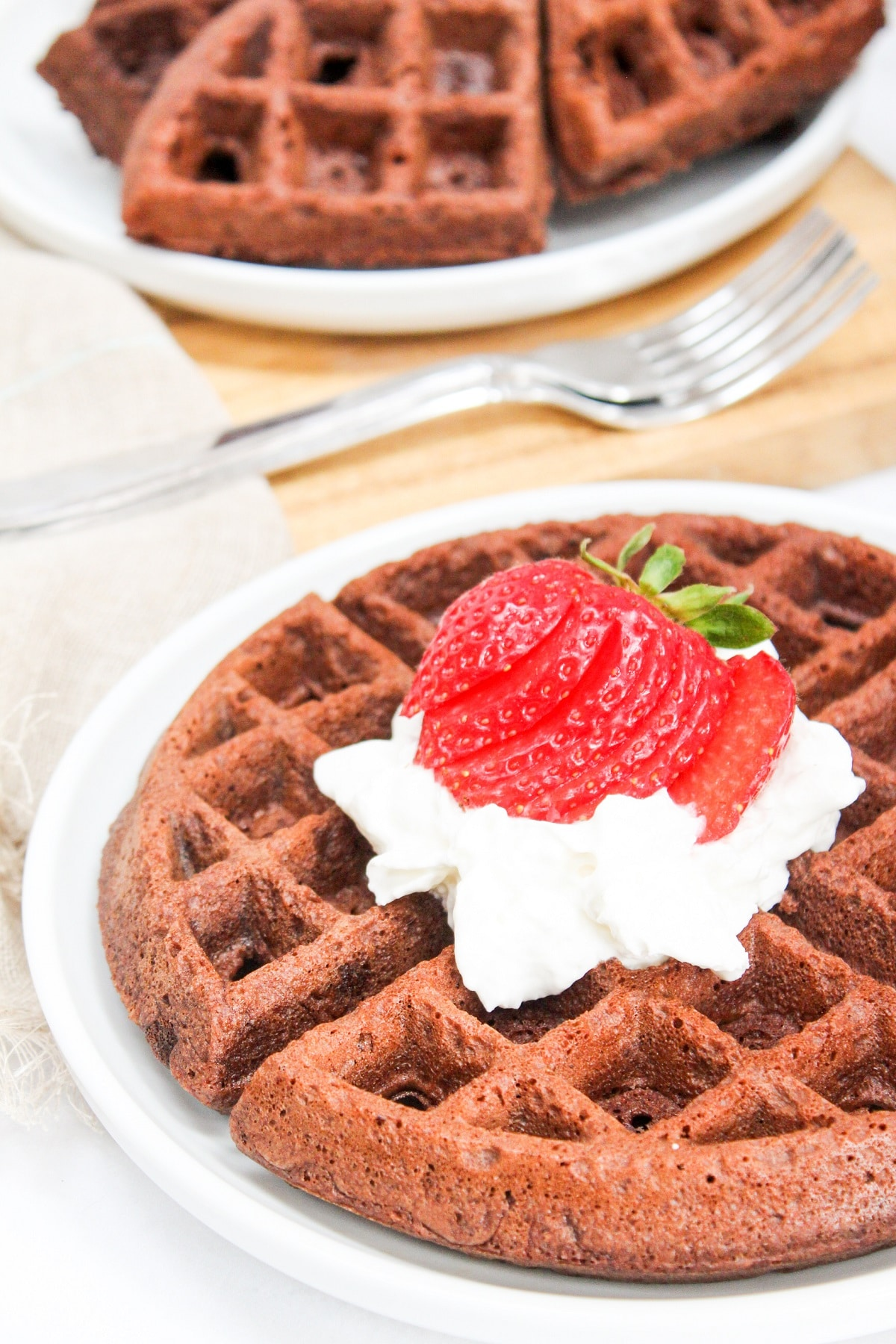 Brownie mix waffles with whipped cream and strawberries on top on a white plate with a plate of waffles in the background