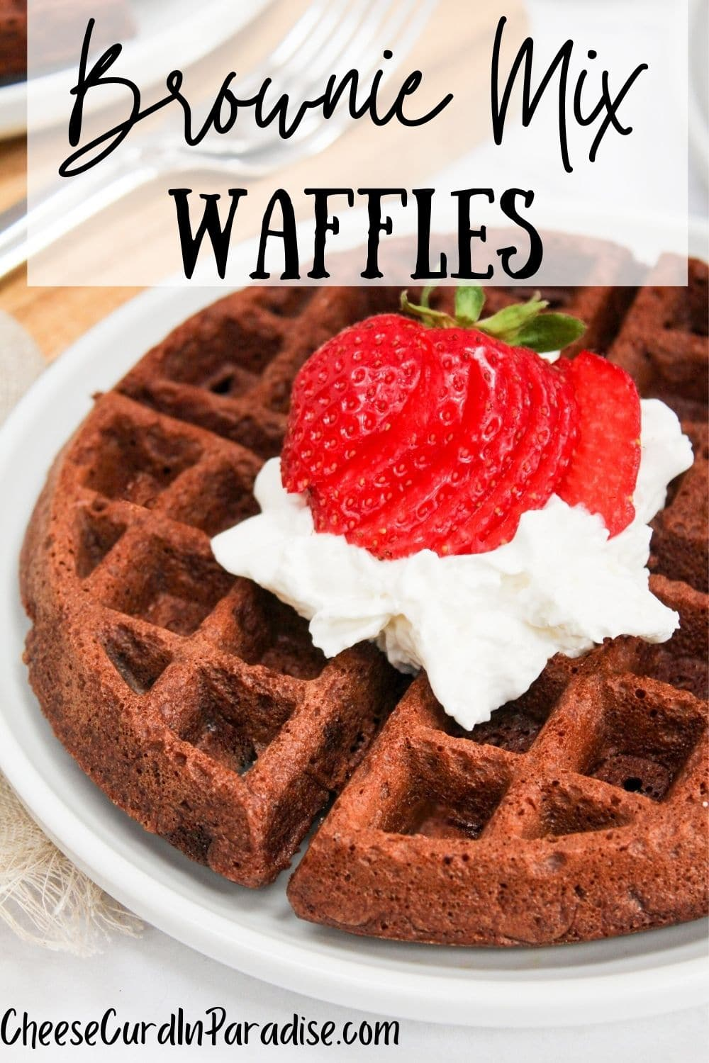 Brownie mix waffles with whipped cream and strawberries on top on a white plate