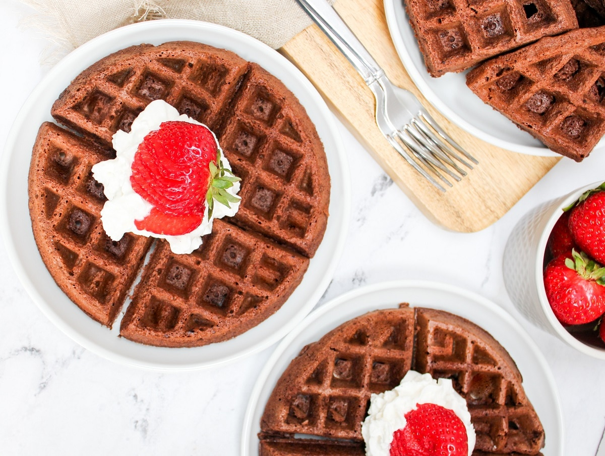 overhead photo of brownie mix waffles topped with whipped cream and strawberries
