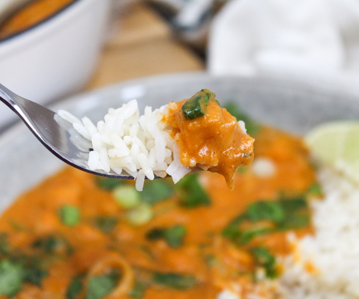 thai butternut squash curry in a bowl with a fork scooping from the contents of the bowl