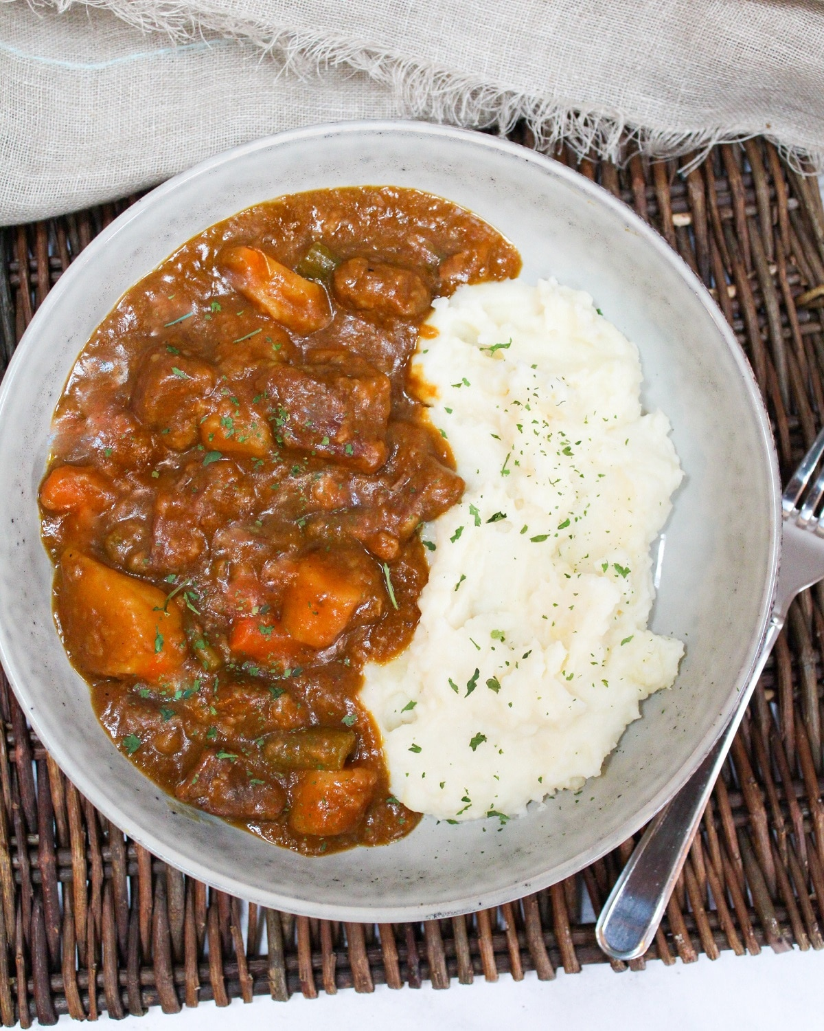 pumpkin beef stew in a gray bowl with mashed potatoes