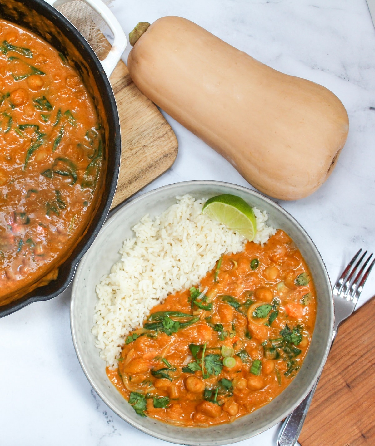 thai butternut squash curry in a bowl with rice next to a skillet with more curry